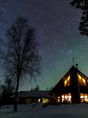 Northern lights peaking behind Winterlake Lodge